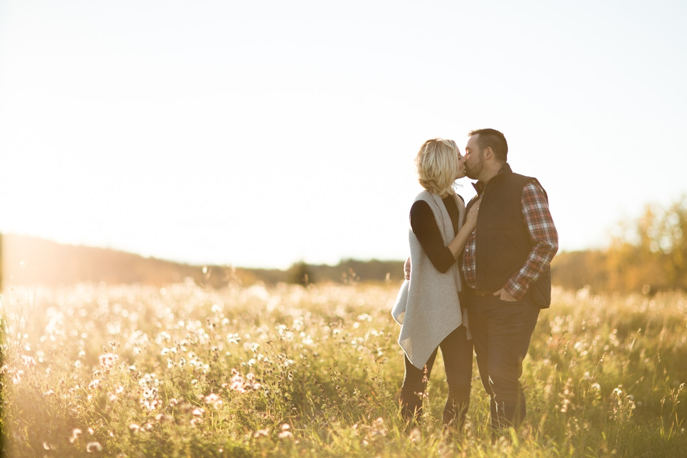 Fall engagement session in Calgary, Alberta with beautiful backlighting and a newly engaged couple kissing as the sun sets