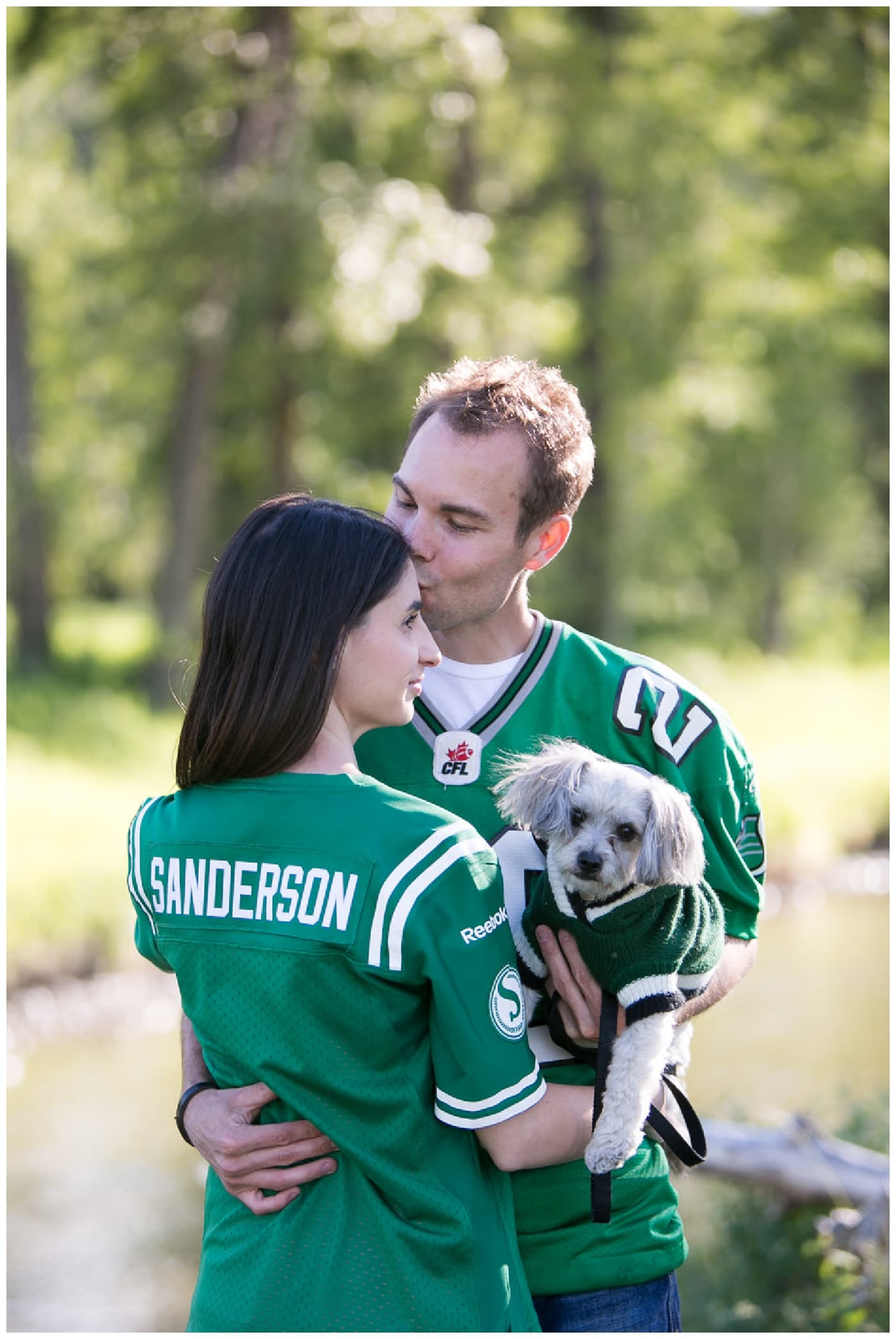Fish Creek Park Engagement with a newly engaged couple and their dog, beautiful green trees, bridegs, and setting sunlight