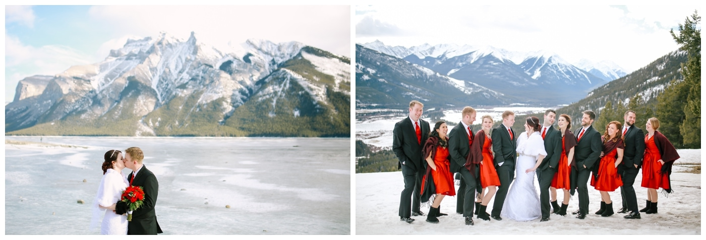 A wedding party dressed in red stands in the Rocky Mountains in Banff with snow at their feet and mountains behind them