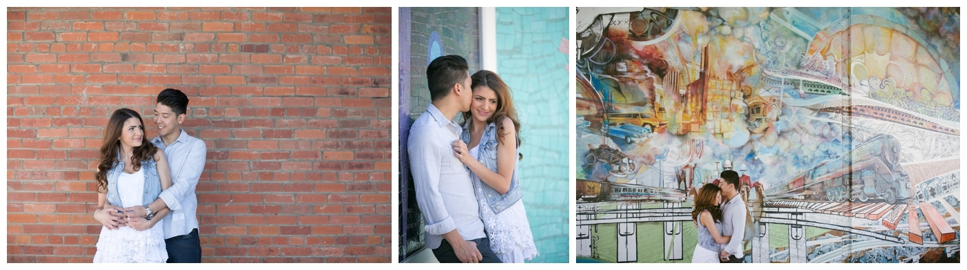 An urban engagement shoot with a couple standing in front of a brick wall and graffiti art