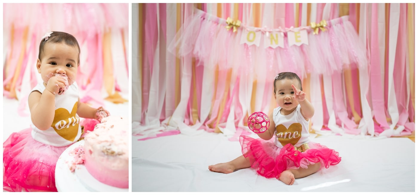 A cake smash shoot of a one-year old Asian girl in a bright pink tulle skirt and a onsie with the word one on it