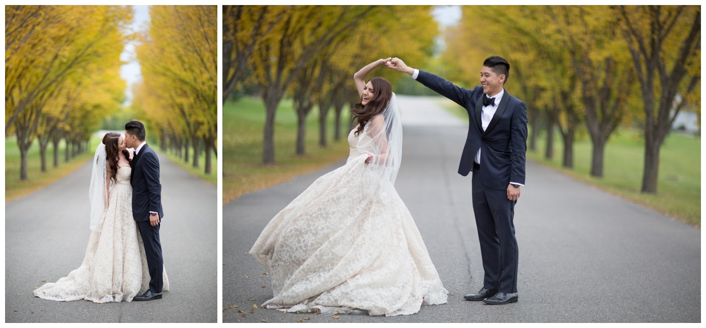 A bride and groom kiss in a roadway lines with beautiful bright yellow fall leaves