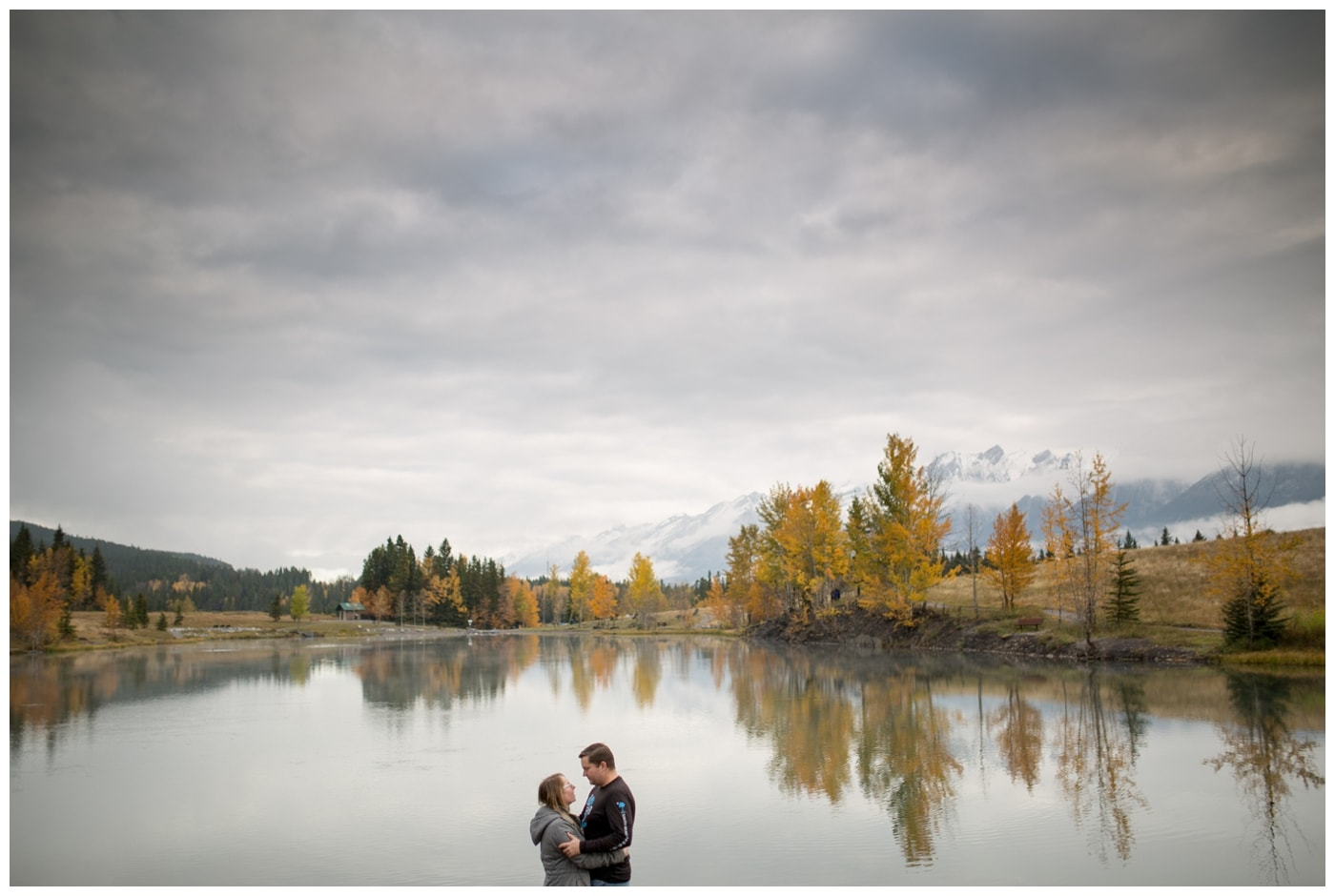 An engagement picture with the couple framed in a lake with mountains in the background, fall trees with bright yellow leaves, and a dramatic sky