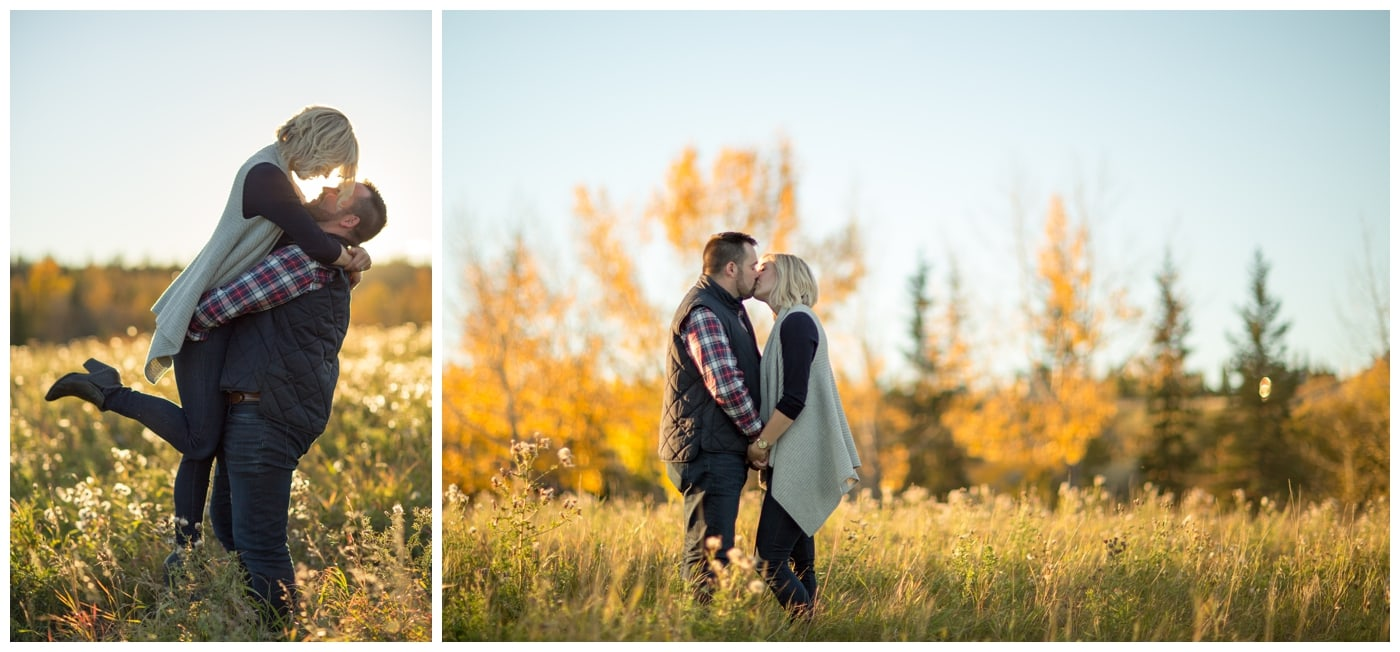 A sunset engagement shoot where the guy is lifting his lady with the sun directly behind them, and kissing in a field with bright yellow autumn trees behind them