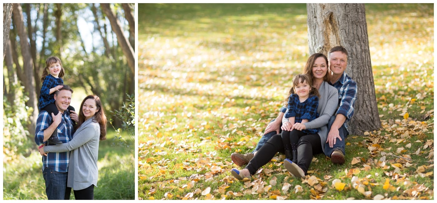 A husband and wife and their young daughter pose in the fall foliage surrounded by trees