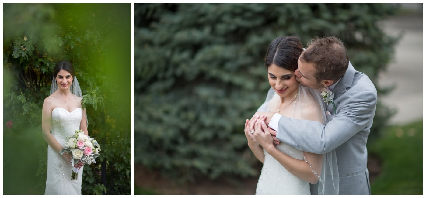 A bride smiles with her bouquet as she is framed by green leaves and kissed gently on the cheek by her husband