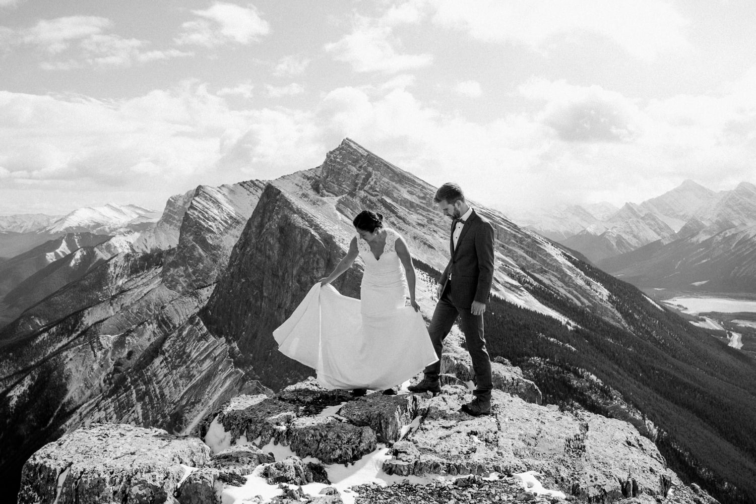 A black and white photo of a couple in wedding attire standing atop a mountain in