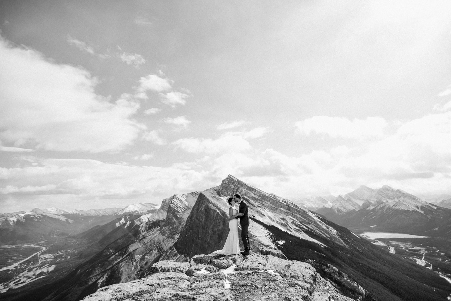 Black and white photo of a couple standing on a mountain with mountains framing behind them